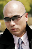 Bald man in business suit looking smart with sunglass