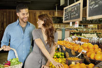 Beautiful young couple looking at each other while shopping in supermarket