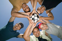 Boy  13-15  with brothers and father holding soccer ball together view from below
