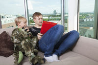 Boy dressed in dinosaur costume sitting with father reading story book on sofa bed at home
