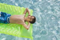 Boy floating in swimming pool on inflatable mattress