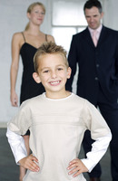 Boy posing for the camera with his parents in the background