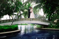 Bride and groom embracing on bridge over swimming pool