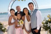 Bride and groom with family on beach  portrait