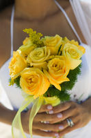 Bride holding yellow rose bouquet  close-up