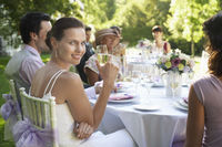 Bride sitting at wedding table holding wineglass smiling
