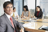 Business man sitting at boardroom table with colleagues portrait