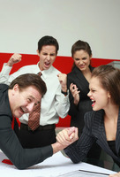 Businessman and businesswoman arm wrestling on table  the others cheering
