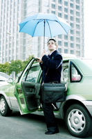 Businessman holding an umbrella while getting out from taxi