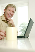 Businessman holding cup while using laptop