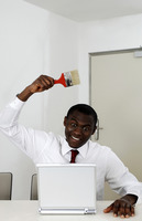 Businessman holding paint brush while using laptop