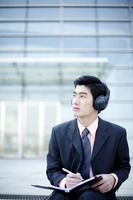 Businessman listening to music on the headphone