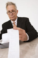 Businessman looking at calculator paper