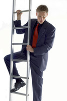 Popular : Businessman looking scared climbing up the ladder