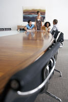 Businesspeople holding a meeting at the end of a conference table