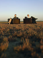 Businesspeople sitting in armchairs on open plain