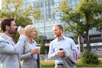 Popular : Businesspeople with disposable cups conversing in city