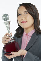 Popular : Businesswoman holding a trophy