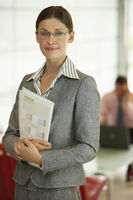 Businesswoman in office holding reports portrait