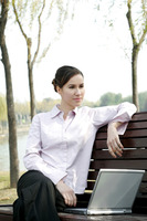Businesswoman sitting on the bench thinking while using laptop