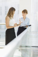 Businesswomen discussing while standing by railing in office