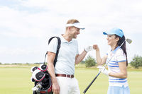 Popular : Cheerful friends giving high-five at golf course