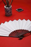 Chinese brush in holder with ink and chinese folding fan at the side