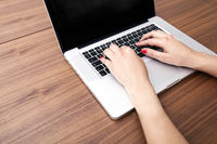 Close-up of businesswoman s hands using laptop at table