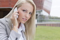 Close-up portrait of beautiful young businesswoman communicating on mobile phone against office building