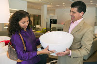 Couple examining large bowl in furniture store