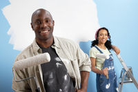Couple holding paint rollers portrait
