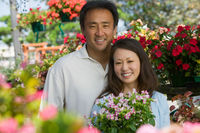 Couple holding plants in plant nursery portrait