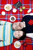 Couple lying on picnic blanket