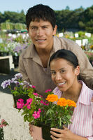 Couple shopping at plant nursery holding flowers portrait