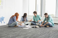 Creative businesspeople discussing while sitting on floor in office