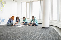 Creative businesspeople working on floor in office