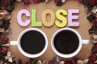 Cup of coffees with close letters