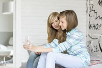 Cute sisters photographing themselves through cell phone at home