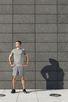 Popular : Determined jogger standing with hands on hips against tiled wall outdoors
