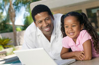 Father and daughter using laptop on patio portrait