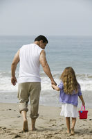 Father and daughter walking on beach