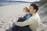Father embracing daughter  5-6  sitting on beach