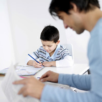 Father reading newspaper with son doing homework in the background