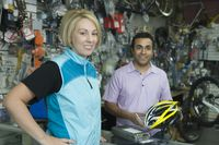 Female cyclist buying helmet at bike shop cash desk