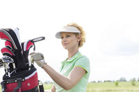 Popular : Female golfer with golf club bag against clear sky