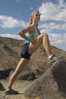 Female jogger stretching in mountains