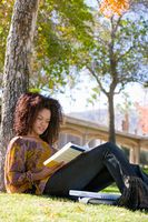 Female student studying under tree