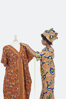 Female tailor in traditional outfit measuring dashiki on tailor s dummy over gray background