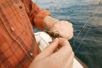 Fisherman baiting hook on boat  close-up