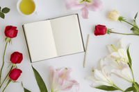 Flatlay of white background with flowers and journal